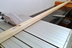Ein Pfosten für ein Seitenteil des Vorratsregals liegt auf der Tischkreisse, um abgelängt zu werden