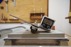 Die ELV Bevel-Box ist mit dem Magnetfuß an einem Hobeleisen befestigt, das in eine Schärfführung eingespannt ist.
