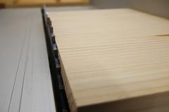 Kiefernholz mit ausrissfreier Schnittkante liegt auf einer Tischkreissäge