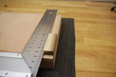 Mit einem Schreinerwinkel wird die Rechtwinkligkeit des Anschlagblocks zur Vorderseite der Grundplatte kontrolliert.