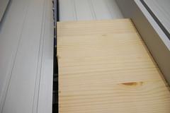 Kiefernholz liegt mit sichtbaren Ausbrüchen an der Rückseite auf einer Tischkreissäge