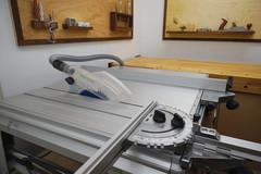 Festool CS 70 EB steht mit montiertem Winkelanschlag und Längsanschlag in einer Werkstatt