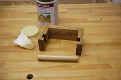 Der geölte Klopapierhalter liegt auf der Werkbank. Daneben ein mit Leinölfirnis getränktes Tuch und eine Dose Leinölfirnis.