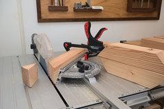 Auf dem Maschinentisch der CS 70 Tischkreissäge ist ein Holzbalken am Winkelanschlag festgezwingt, um eine Gehrung zu sägen