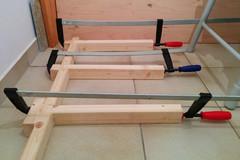 Drei Querverbinder werden mithilfe von Schraubzwingen mit einem Seitenpfosten verleimt.