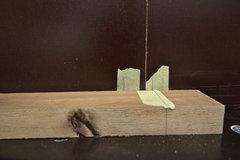 Auf dem Frästisch wird eine Nut in ein Stück Akazienholz gefräst