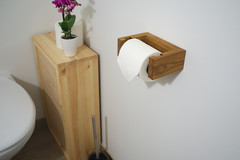 Der Klopapierhalter mit einer Klopapierrolle bestückt an der Wand montiert.