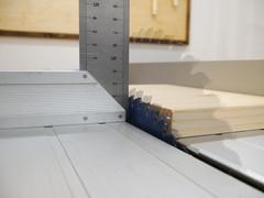 Sägeblatt einer Tischkreissäge in unterschiedlichen Höheneinstellungen als Mehrfachbelichtung übereinandergelegt. Daneben ein Tischlerwinkel, der die Höhe anzeigt.